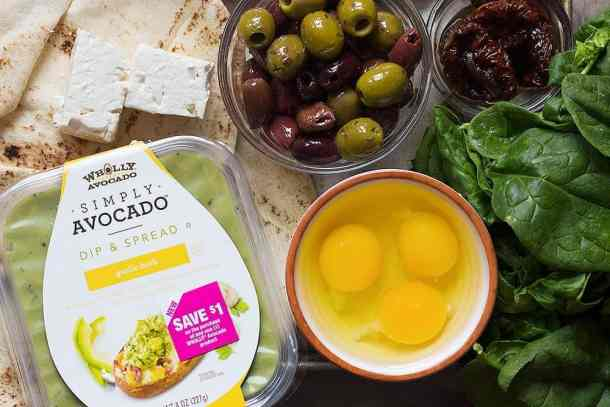 to make avocado egg breakfast you need avocado spread, olives, eggs, sun dried tomatoes, spinach, feta cheese and pita bread.