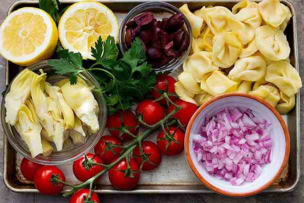 The ingredients to make greek tortellini salad are tortellini, artichoke. kalamata olives, red onion, lemon, parsley and tomatoes.