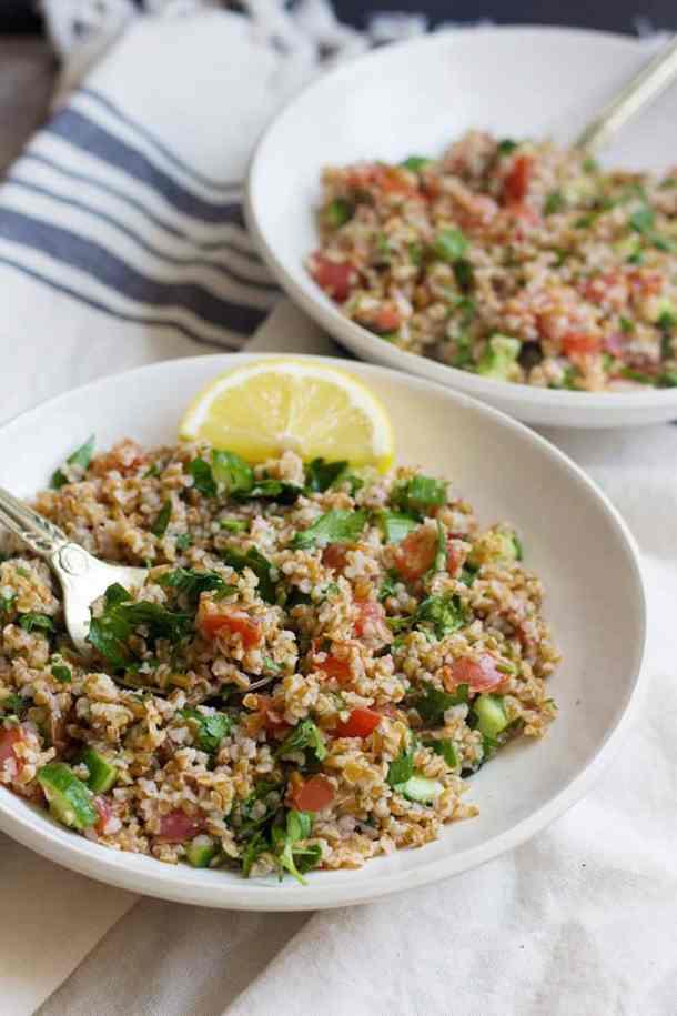 Serve tabbouleh salad in bowls with a slice of lemon.