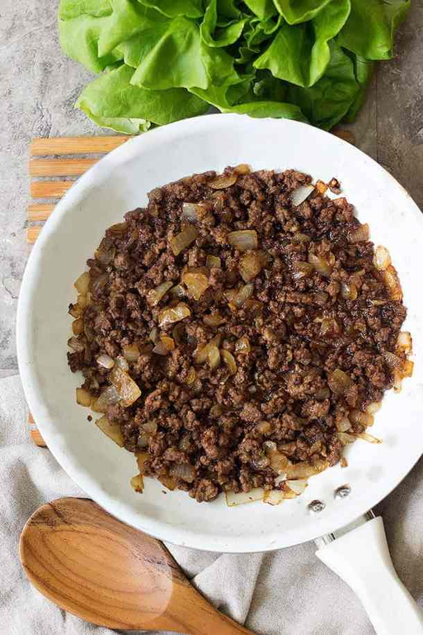 To make Korean ground beef recipe, saute onion and ground beef with garlic and then add soy sauce and sugar.