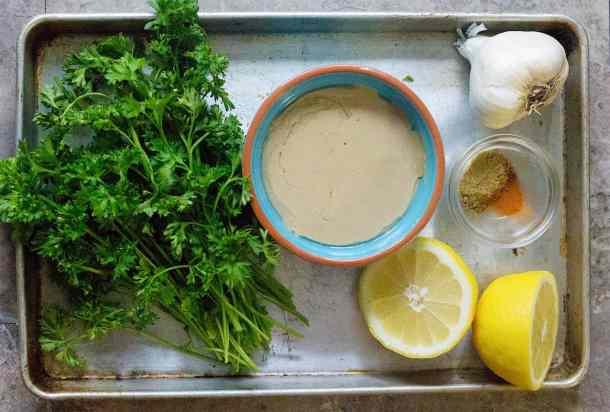 To make tahini dressing you need tahini, lemon, spices, garlic and parsley.