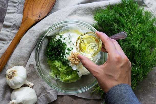 To make tzatziki sauce recipe mix grated cucumbers, dill, yogurt and garlic in a bowl then add in olive oil.