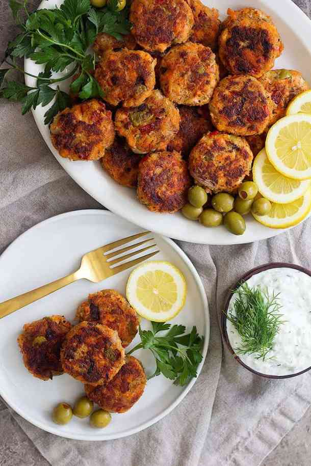 Homemade salmon patties in a platter with olives, lemon and parsley.