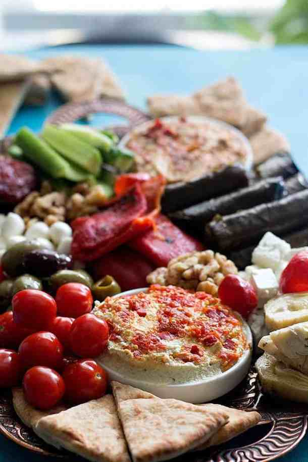 A Mediterranean platter with hummus, cheese, olives and other items.