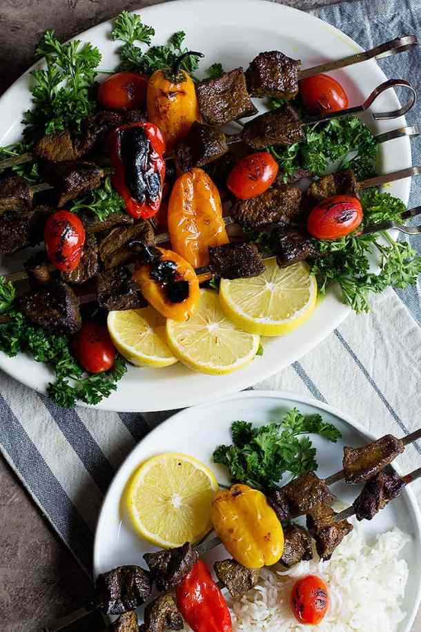 Beef shish kabob on a white plate with tomatoes and peppers.