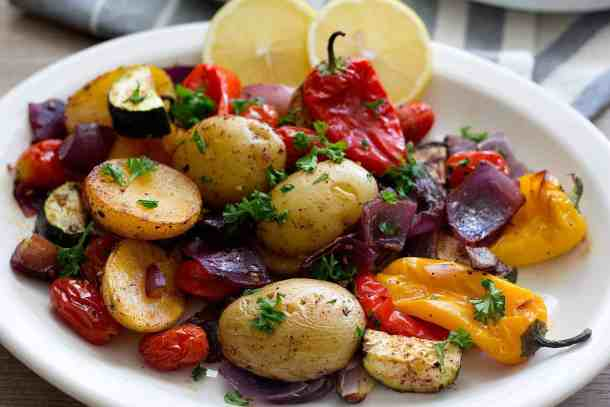 oven roasted vegetables made with potatoes onions, tomatoes and peppers.