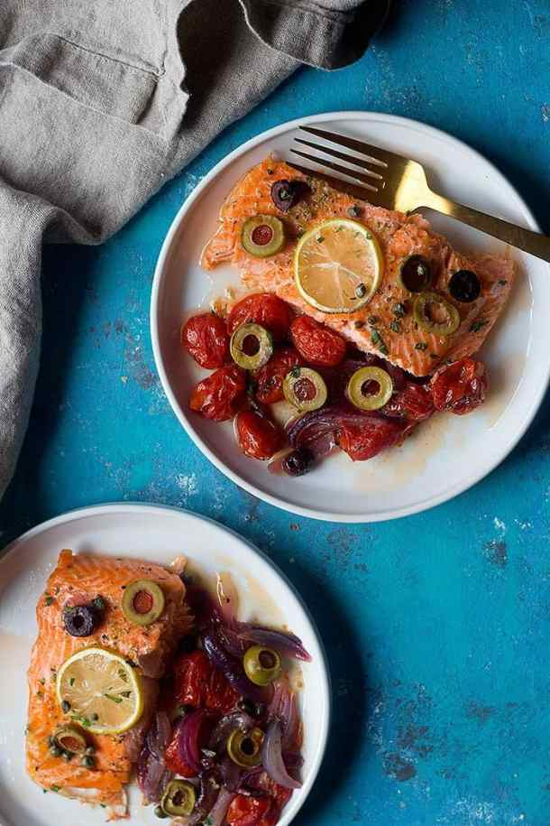 Serve baked salmon with lemons immediately.