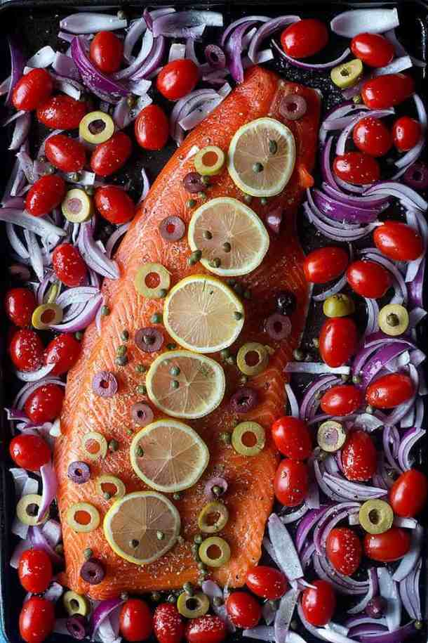 Place salmon on the baking sheet and top with lemon and capers and olives. Bake with tomatoes and onions.