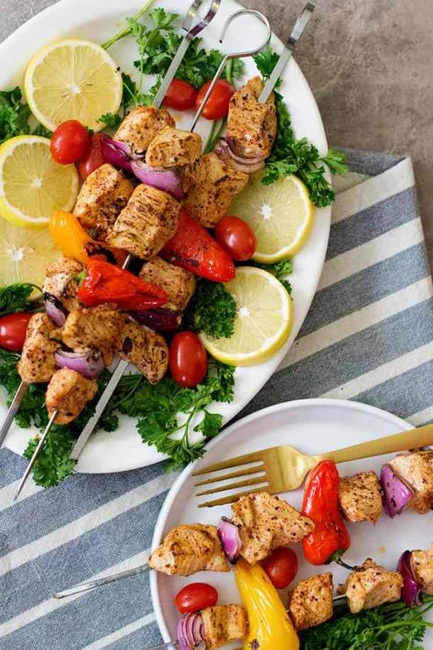 grilled chicken shish kabob on a plate with lemon and tomatoes.