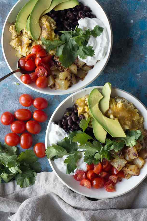 Enjoy this easy and tasty Mexican-inspired breakfast bowl made with fresh ingredients. Delicious scrambled eggs and home fries make a tasty bowl topped with fresh avocado and tomatoes.