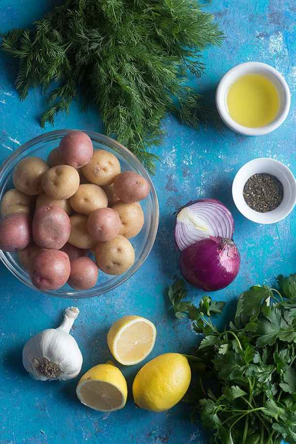 Ingredients to make Mediterranean potato salad: potatoes, dill, parsley, red onion, garlic, zaatar, olive oil and lemon juice