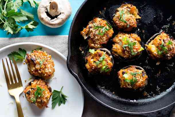 Crab stuffed mushrooms in a cast iron skillet and on a white plate.