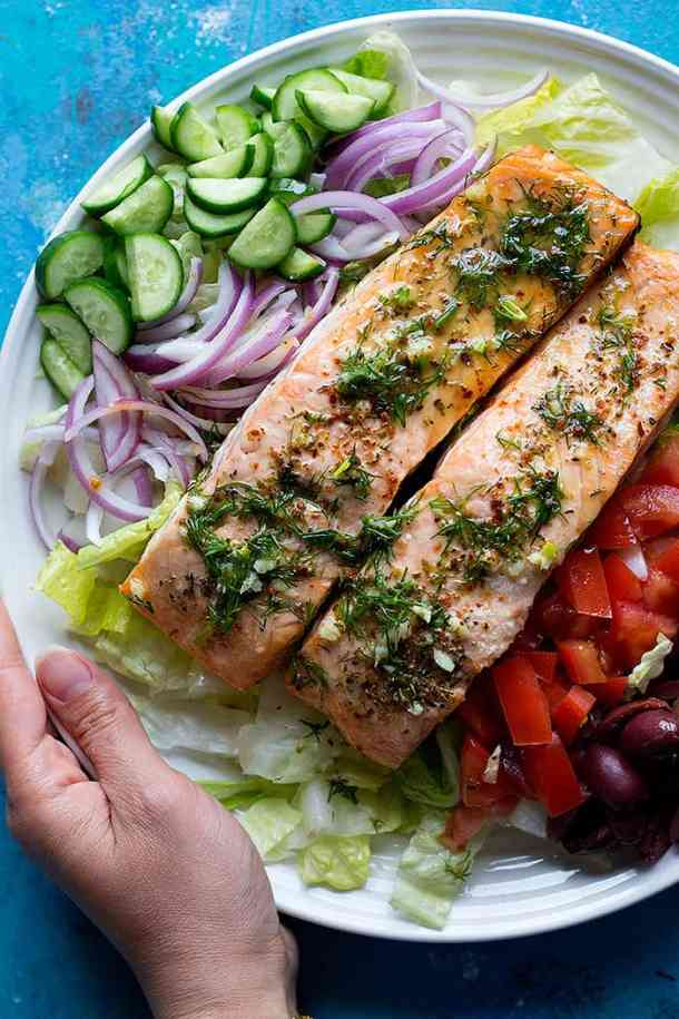 Greek salmon salad on a plate with cucumbers and onions