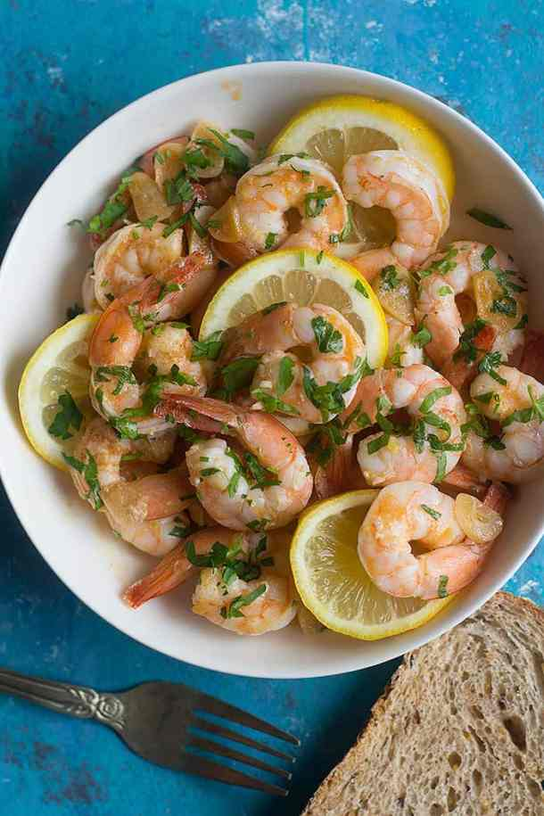 lemon shrimp made with garlic olive oil and served in a bowl. Topped with chopped parsley.