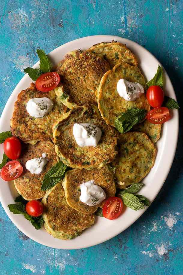 fritters made with zucchini set on a plate, topped with yogurt and cherry tomatoes.