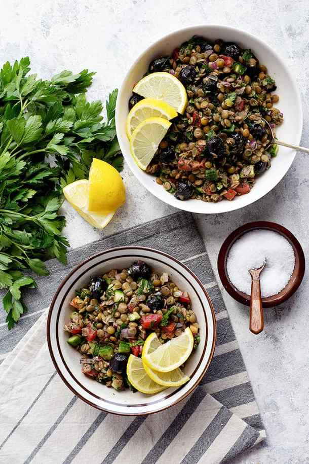 Two bowls of Greek lentil salad with lemon slices and a bunch of parsley.