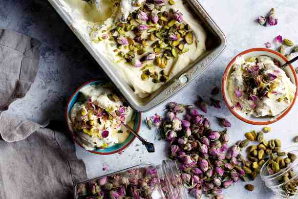 Two bowls of saffron ice cream with a loaf pan full of ice cream topped with pistachios and roses.