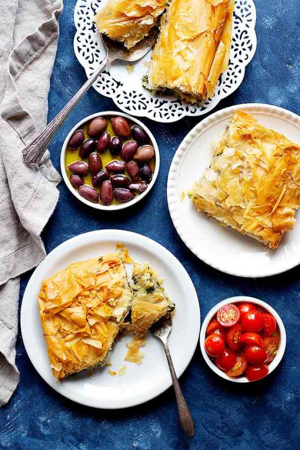 Three plates of authentic spanakopita with olives in olive oil and tomatoes.