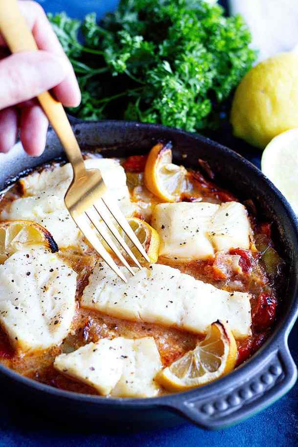Baked cod in a clay pan with tomatoes, onions and peppers.