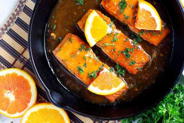 three salmon fillets in a pan with orange sauce.