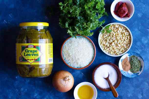 Ingredients shot grape leaves, rice, onion, olive oil, parsley, spices, pine nuts and tomato paste