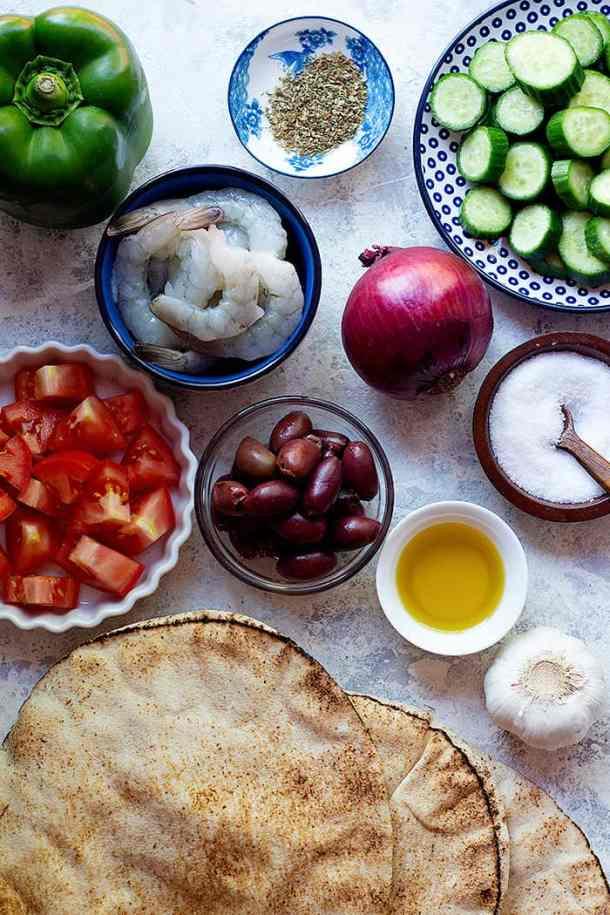 to make no mayo shrimp salad you need shrimp, tomatoes, onion, cucumber, oregano, olive oil and olives.