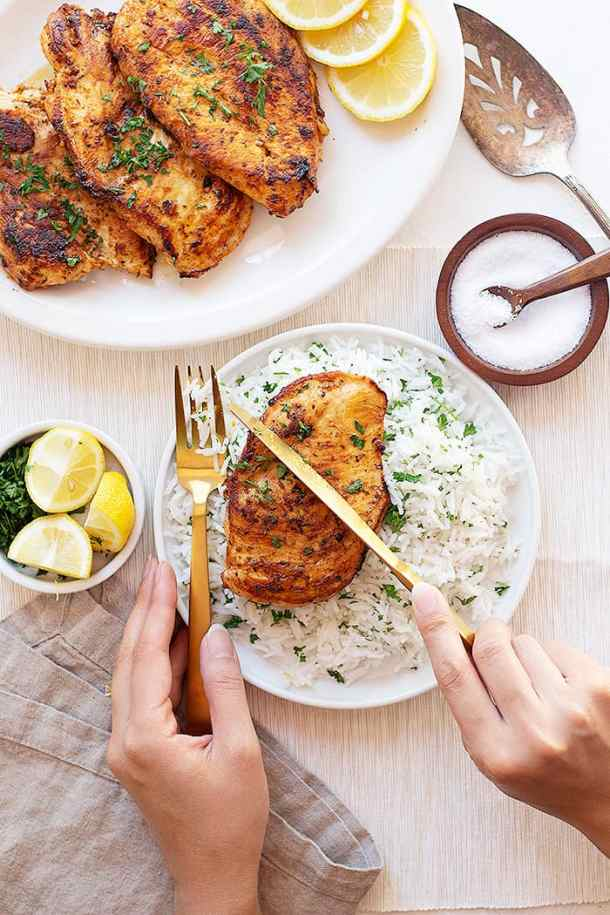 two plates of garlic lemon chicken with herb rice.