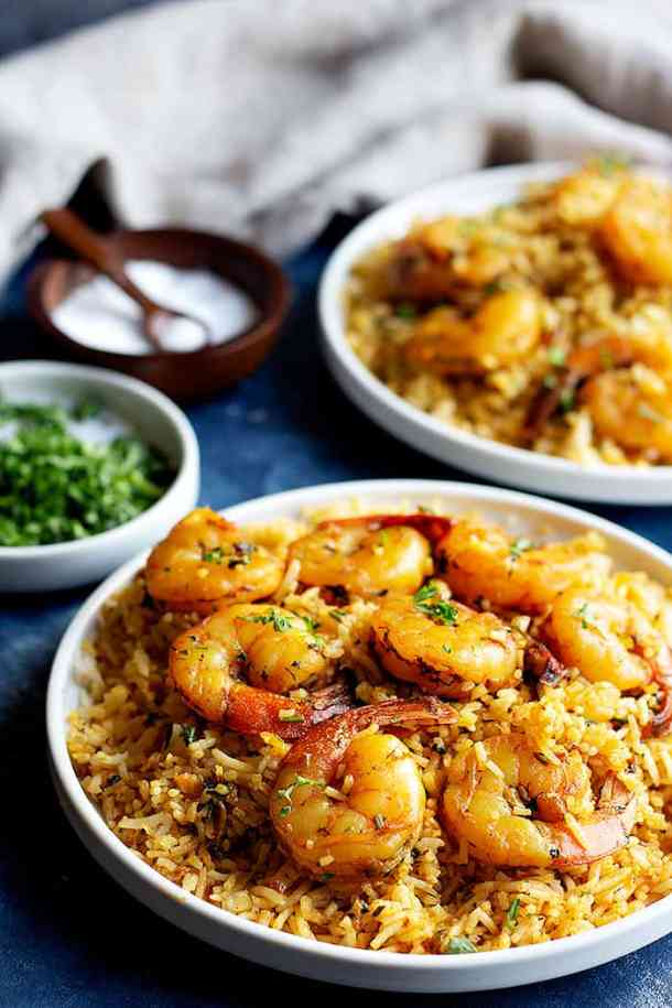 two shrimp and rice dishes on a blue surface with salt and cilantro and a napkin.