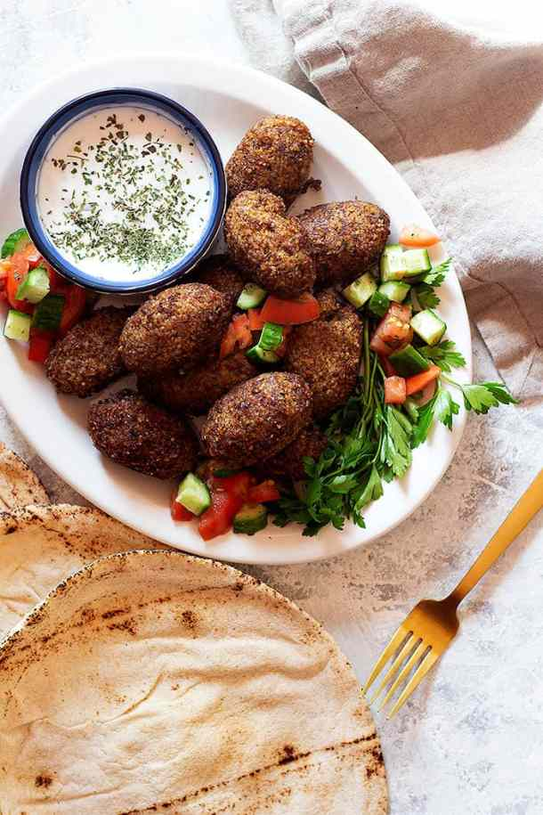 fried kibbeh is shaped like a football or a croquette.