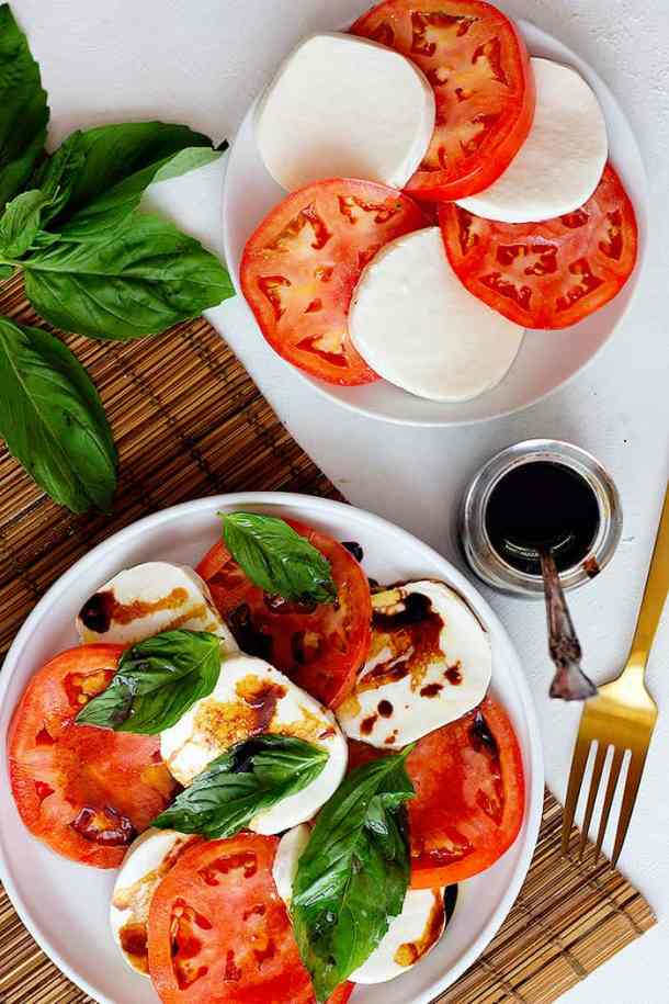 Two plates on a white surface, one has tomatoes and mozzarella and the other has caprese salad topped with balsamic vinegar.