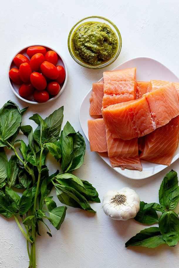 To make this recipe, you need salmon, pesto, tomatoes, basil and garlic.