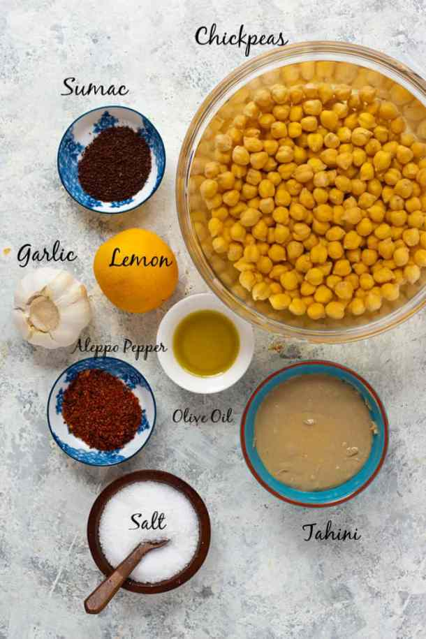 To make homemade hummus, you need chickpeas, sumac, lemon, garlic, tahini, olive oil, Aleppo pepper and salt.