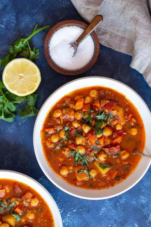 A bowl of Moroccan chickpea stew served with lemon juice and topped with parsley.