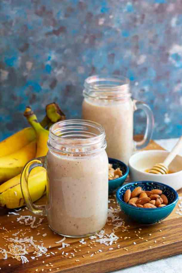 Two glasses of banana date shake with fruit and nuts on the background.