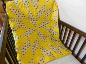 handmade baby quilt in yellow with a star design.