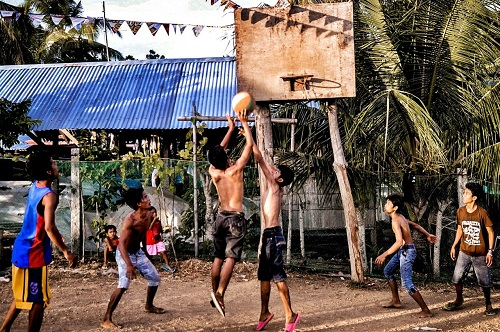 Young Filipino men playing basketball in a makeshift court and showing how much Filipinos love basketball