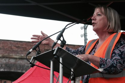 Photograph of Penny Hicks (The People's Assembly Against Austerity) addressing NO MORE AUSTERITY demonstrators at Castle Arena, Manchester.