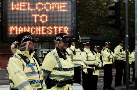 """Photograph of Police Officers standing next to """"WELCOME TO MANCHESTER"""" signage along NO MORE AUSTERITY march route from Castlefield Arena to Piccadilly Gardens, Manchester. 1st October 2017."""