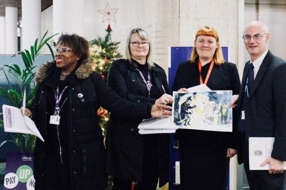 Photograph of UNISON members, Councillor Helen McDonald and Councillor Kevin Robinson hold a Christmas card signed by the people of Southend demanding an end to Scrooge-like pay rises.