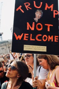 Photograph of placard reading: TRUMP NOT WELCOME (because he's a racist, sexist, xenophobic, imperialist bigot).
