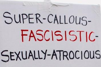 Photograph of placard reading: Super–Callous–Fascisistic[sic]–Sexually–Atrocious