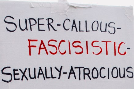 Photograph of placard reading: Super–Callous–Fascisistic[sic]–Sexually–Atrocious