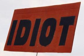 Photograph of placard reading: Idiot