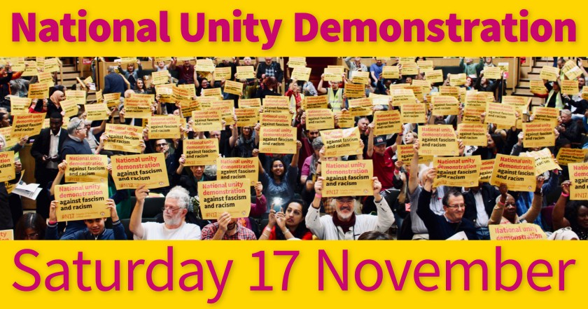 """Photograph showing a large group of STAND UP TO RACISM International Conference attendees holding National Unity Demonstration posters above their heads as a sign of support – the accompanying text reads: """"National Unity Demonstration Saturday 17 November."""""""