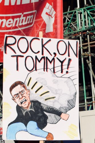 "Photograph of placard reading ""ROCK, ON TOMMY"" with a cartoon below depicting a large rock squashing vile racist Tommy Robinson."
