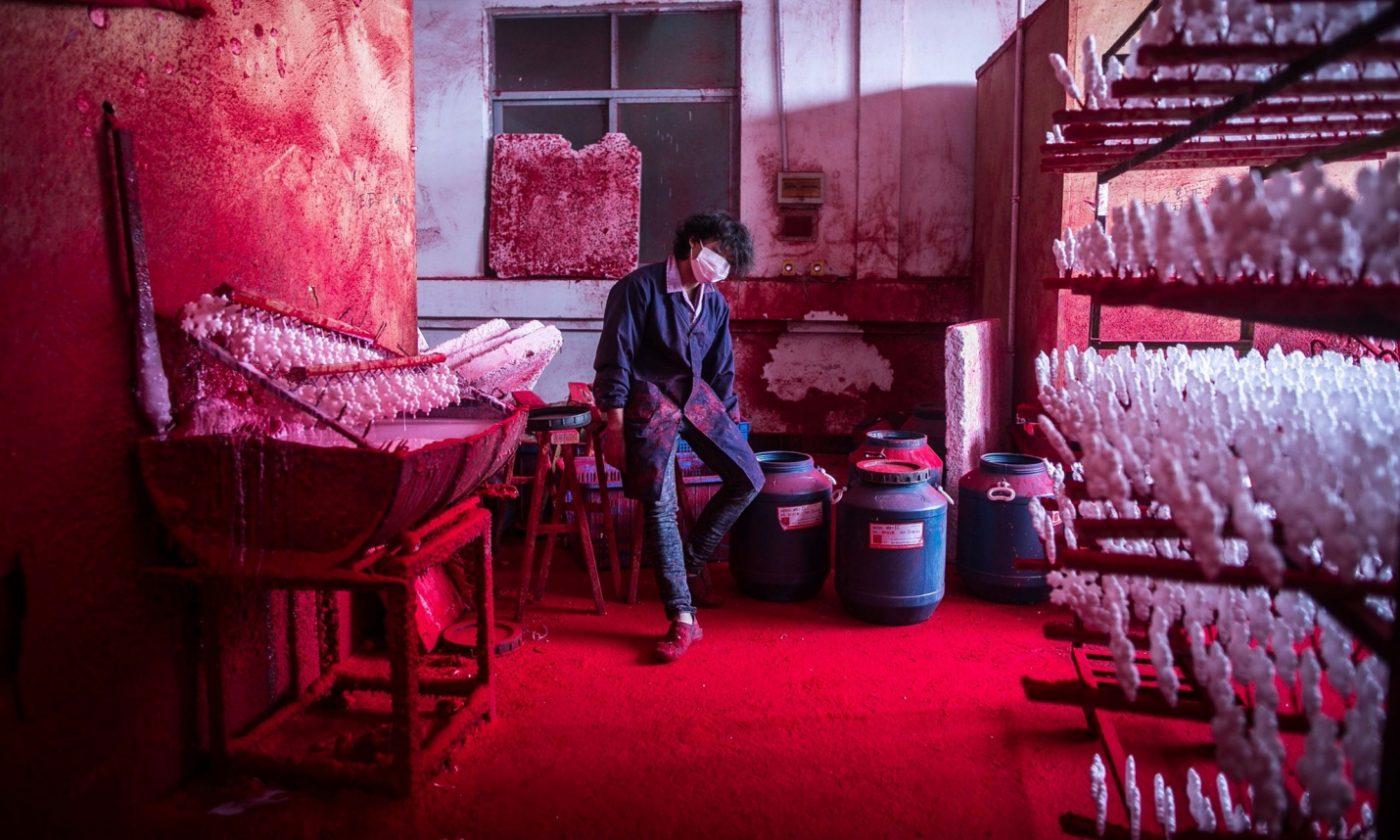 Wei usa 10 máscaras al día para protegerse del polvo que utiliza para pintar las decoraciones navideñas. Foto: Imaginechina/Rex