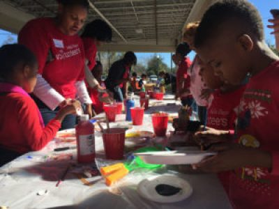 """Volunteers work on painting """"peace tiles"""" to help beautify a community center."""