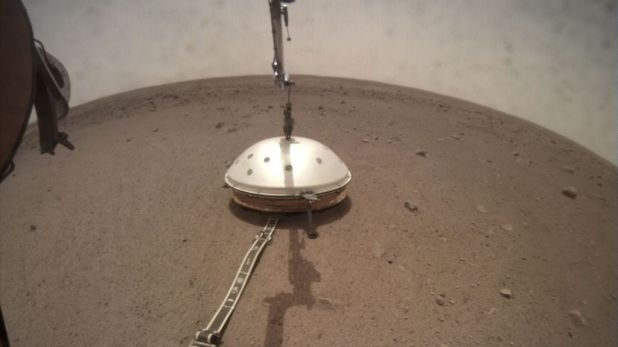 The InSight Lander seismometer under its protection against the wind and the heat shield. Image credit: NASA / JPL-Caltech