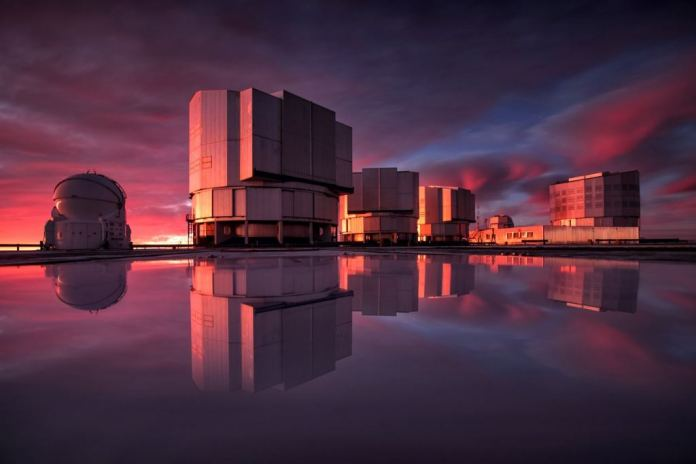 ESO's Very Large Telescope (VLT) has recently received an upgraded addition to its suite of advanced instruments. On 21 May 2019 the newly modified instrument VISIR (VLT Imager and Spectrometer for mid-Infrared) made its first observations since being modified to aid in the search for potentially habitable planets in the Alpha Centauri system, the closest star system to Earth. This stunning image of the VLT is painted with the colours of sunset and reflected in water on the platform. While inclement weather at Cerro Paranal is unfortunate for the astronomers using it, it lets us see ESO's flagship telescope in a new light. Image Credit: ESO/VLT