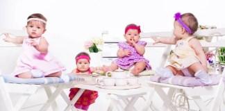 4 bambine di pochi mesi, perfettamente vestite, che prendono un thè